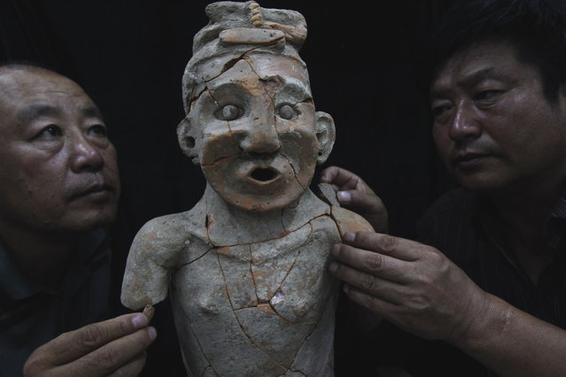 Archaeologists repair a pottery statue found in Aohan Banner, North China's Inner Mongolia autonomous region, July 3, 2012. (Photo by Xinhua)