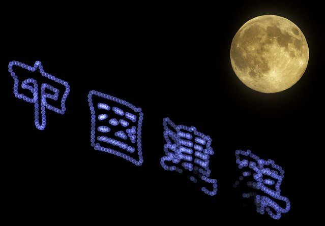 """The """"Supermoon"""" rises over a construction site  in Beijing. The phenomenon, which scientists call a perigee moon, occurs when the moon is near the horizon and appears larger and brighter than other full moons. (Photo by Andy Wong/Associated Press)"""