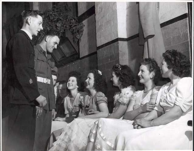 Wes Colquhoun and Fred Phair talking to the girls at the ball in the Soldier's Memorial Hall, Drouin, Victoria, ca. 1944. Pride of the stag line at Drouin's weekly dance were bachelors – gay Warrant Officer Wes Colquhoun (23), R.A.A.F., and Corporal Fred Phair (25), A.I.F. Wes, son of Drouin's butcher, was sole surviving member of a Lancaster Crew... Fred, son of Drouin's fruiterer, served in New Guinea...