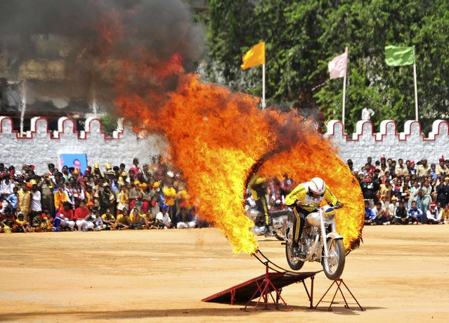 An Indian army soldier performs a stunt on his motorcycle during India's Independence Day celebrations in the southern Indian city of Bangalore August 15, 2014. (Photo by Abhishek N. Chinnappa/Reuters)