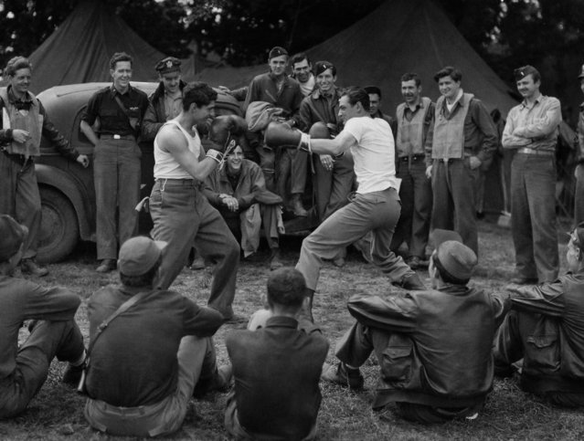 Lt. Col. Jim Daley, right, of Amarillo, Tex., and Lt. Sumner Calish, of Boston, Mass., engage in a bout of fisticuffs by way of relaxation between sorties from a U.S. 9th A.F. Fighter group base in France on August 28, 1944. (Photo by Fred Namage/AP Photo)