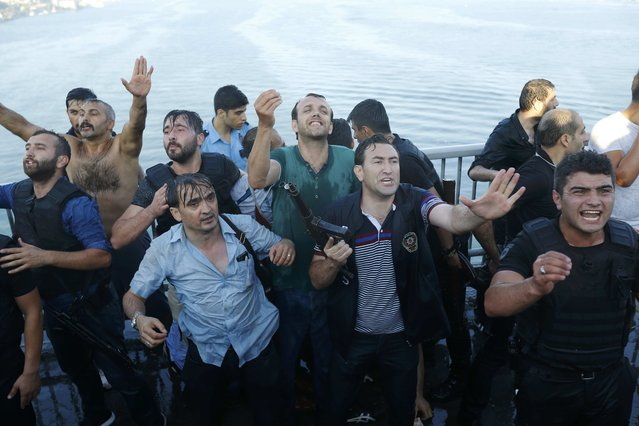 Policemen protect a soldier from the mob after troops involved in the coup surrendered on the Bosphorus Bridge in Istanbul, Turkey July 16, 2016. (Photo by Murad Sezer/Reuters)
