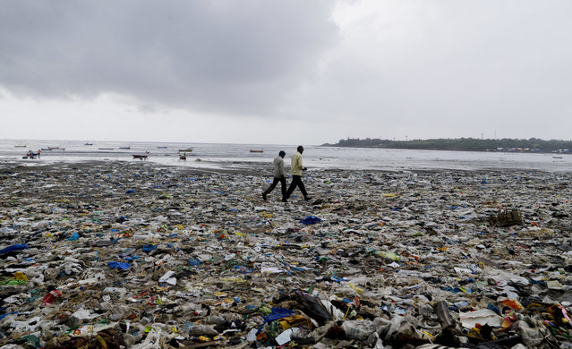 In this August 19, 2017 photo, people walk past garbage at the Versova beach on the Arabian Sea coast in Mumbai, India. The 2.5-kilometer (approximately 1.5 miles) stretch of Mumbai's Versova beach was littered with plastic water bottles, discarded plastic bags and containers, empty packets of chips, and more plastic wrappers. According to government estimates, each one of India's 1.3 billion citizens generates roughly 0.2 to 0.6 kilograms (approximately 0.44 to 1.3 pounds) of waste each day. (Photo by Rajanish Kakade/AP Photo)