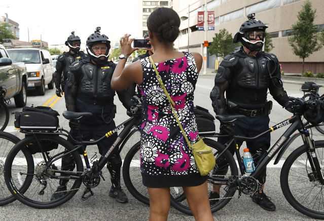 A demonstrator takes a picture of the police line during the Shut Down Trump & the RNC protest on Sunday, July 17, 2016, in Cleveland. The Republican National Convention starts Monday. (Photo by John Minchillo/AP Photo)