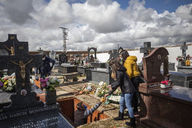 Family members, right, attend the burial of Rosalia Mascaraque, 86, during the coronavirus outbreak in Zarza de Tajo, central Spain, Wednesday, April 1, 2020. (Photo by Bernat Armangue/AP Photo)