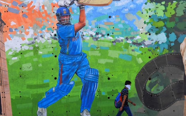 """A man wearing a facemask as a preventive measure against the COVID-19 coronavirus walks past a mural of former Indian cricketer Sachin Tendulkar in Mumbai on March 19, 2020. Indian legend Sachin Tendulkar has offered an unusual take on the coronavirus fight by comparing it to Test cricket, urging patience and teamwork, and warning """"we have to defend well"""". (Photo by Indranil Mukherjee/AFP Photo)"""