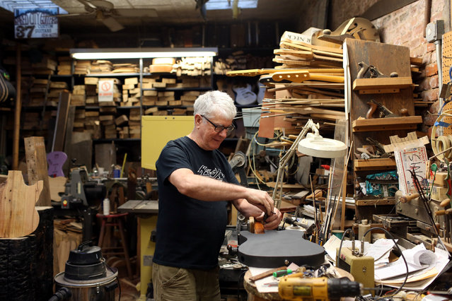"Rick Kelly, owner of Carmine Street Guitars, works on a guitar made from discarded yellow and white pine wood at his shop in New York City, U.S., July 21, 2016. Kelly builds custom guitars from the ""bones of New York"", using reclaimed lumber from historic New York buildings. (Photo by Joe Penney/Reuters)"