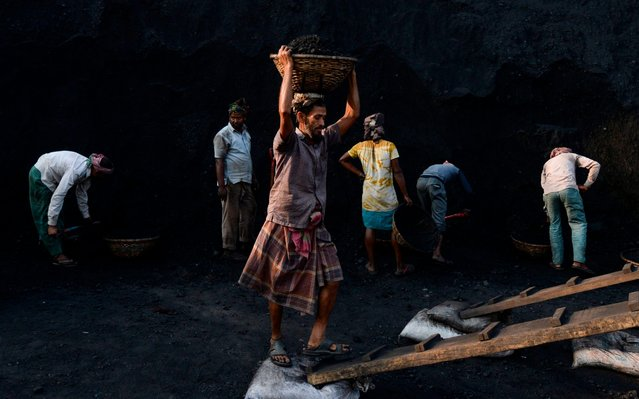 Labourers unload coal off a cargo ship on the outskirts of Dhaka on February 10, 2020. (Photo by Munir Uz Zaman/AFP Photo)