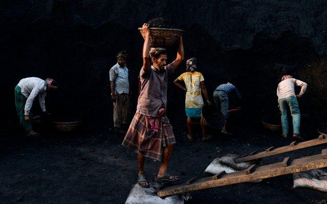 Labourers unload coal off a cargo ship on the outskirts of Dhaka on February 10, 2020. (Photo by Munir Uz Zaman/AFP Photo)