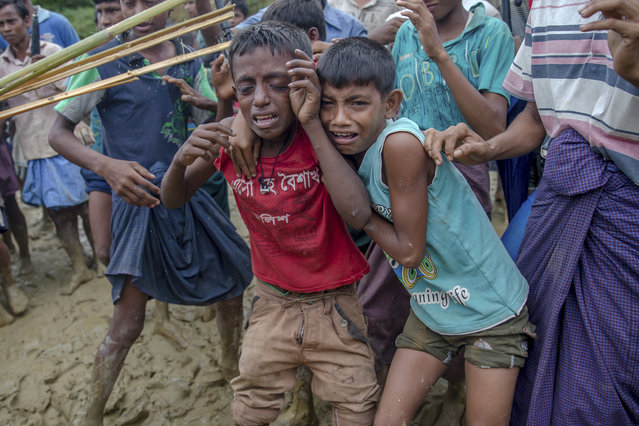 In this Wednesday, September 20, 2017, file photo, Rohingya Muslim boys, who crossed over from Myanmar into Bangladesh, cry as Bangladeshi men push them away during distribution of food aid near Balukhali refugee camp, Bangladesh. Children make up about 60 percent of the sea of humanity that has poured in to Bangladesh over the last four weeks fleeing terrible persecution in Myanmar. And the UN's child rights agency UNICEF has so far counted about 1,400 children who have crossed the border without their parents. (Photo by Dar Yasin/AP Photo)
