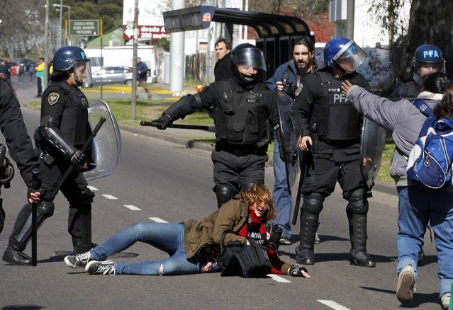 Photographer Maria Pirsch falls on the road after being hit by anti-riot policemen during a protest staged by state-run workers who were seeking to block a road in Buenos Aires August 27, 2014. Opposition labour unions have planned a 24-hour strike across Argentina for Thursday to press President Cristina Fernandez de Kirchner's administration for wage increases in line with inflation rate and to reduce the tax income in salaries. (Photo by Enrique Marcarian/Reuters)