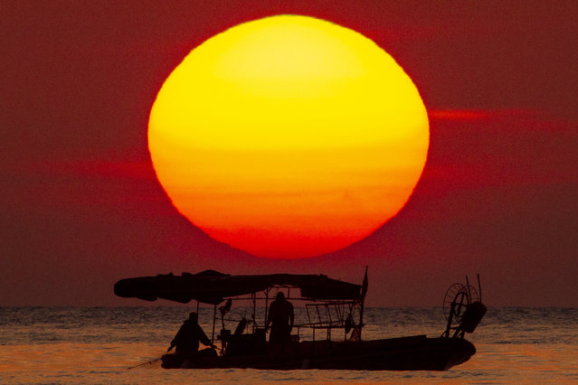 The sun sets as a fishing boat crosses the Mediterranean Sea at Ramlet al-Baida public beach, which is almost empty of people during a lockdown aimed at curbing the spread of the COVID-19 coronavirus, in Beirut, Lebanon, Saturday, April 18, 2020. (Photo by Hassan Ammar/AP Photo)