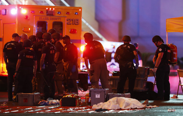 A body is covered with a sheet after a mass shooting in which dozens were killed at a music festival on the Las Vegas Strip on Sunday, October 1, 2017. (Photo by Steve Marcus/Las Vegas Sun via AP Photo)