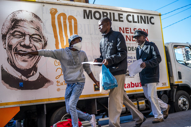 A volunteer directs two men towards a medical tent where they will be tested for COVID-19 as well as HIV and Tuberculosis, in downtown Johannesburg Thursday, April 30, 2020. Thousands are being tested in an effort to derail the spread of coronavirus. South Africa will began a phased easing of its strict lockdown measures on May 1, although its confirmed cases of coronavirus continue to increase. (Photo by Jerome Delay/AP Photo)