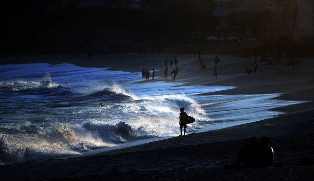 A surfer walks along the shore at a beach in Barra, west of Rio de Janeiro on August 1, 2016 ahead of the Rio 2016 Olympic Games. (Photo by Jewel Samad/AFP Photo)