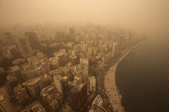 A sandstorm shrouds the capital city of Beirut, Lebanon, Tuesday, September 8, 2015. The unseasonal sandstorm hit Lebanon and Syria, reducing visibility and sending dozens to hospitals with breathing difficulties because of the fine dust. (Photo by Hussein Malla/AP Photo)
