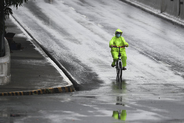 A man wearing a protective mask and raincoat rides his bicycle during rain caused by typhoon Vongfong in Manila, Philippines Philippines on Friday May 15, 2020. More than 150,000 people were riding out a weakening typhoon in emergency shelters in the Philippines on Friday after a mass evacuation that was complicated and slowed by the coronavirus. (Photo by Aaron Favila/AP Photo)
