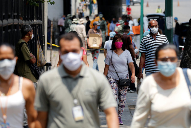 People wearing protective masks walk on a street during a nationwide quarantine as the spread of the coronavirus disease (COVID-19) continues, in Caracas, Venezuela on April 20, 2020. (Photo by Manaure Quintero/Reuters)