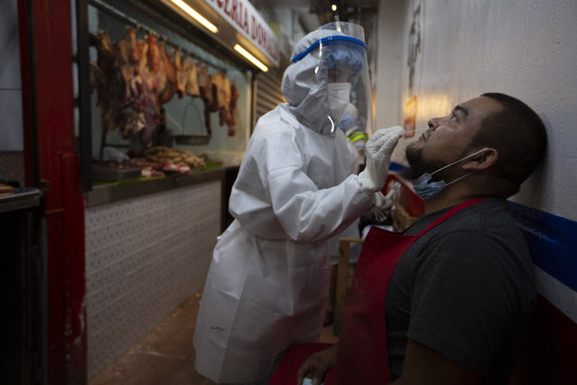 A medical worker from the Ministry of Health wearing a protective suit takes a sample to test for COVID-19 from a butcher at La Terminal market in Guatemala City, Thursday, May 21, 2020. (Photo by Moises Castillo/AP Photo)