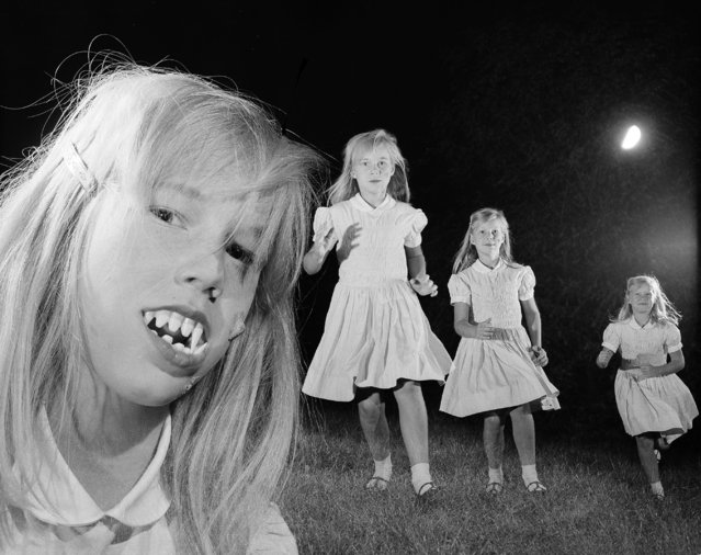 With the help of some fake teeth and multiple exposures, New York AP photographer Eddie Adams' daughter Susan is transformed into a little ghoul on Halloween night, October 31, 1966. (Photo by Eddie Adams/AP Photo)