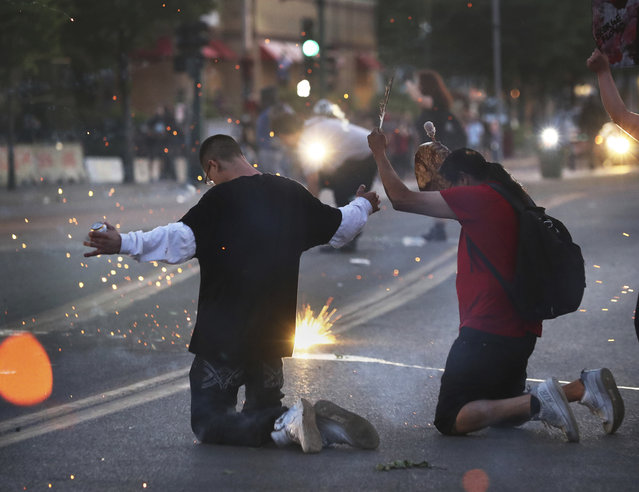 A concussion grenade goes off as protesters kneel, including a Native American man named John holding an eagle feather and hand drum, outside the Minneapolis police 3rd Precinct on Thursday, May 28, 2020, during a third night of unrest following the death of George Floyd in Minneapolis police custody. (Photo by David Joles/Star Tribune via AP Photo)