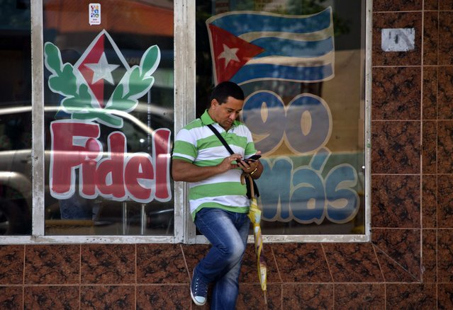 A man surfs the internet with his cell phone backdropped by decorated storefront windows celebrating Fidel Castro's upcoming 90th birthday, in Havana, Cuba, Friday, August 12, 2016. (Photo by Ramon Espinosa/AP Photo)
