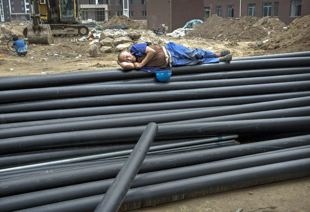 A Chinese construction worker sleeps on piping as he takes a break at the building site of a new apartment complex on August 29, 2014 in Beijing, China. (Photo by Kevin Frayer/Getty Images)