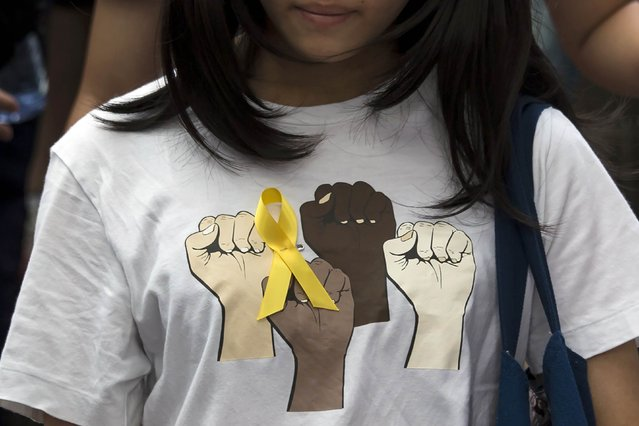 A secondary school student wears a yellow ribbon pinned to her T-shirt during a rally against Beijing's election framework for Hong Kong, outside the government headquarters in Hong Kong September 26, 2014. Hundreds of school children joined university students demanding greater democracy on Friday, capping a week-long campaign that has seen a large cut-out depicting Hong Kong's leader as the devil paraded through the city and calls for him to resign. (Photo by Tyrone Siu/Reuters)