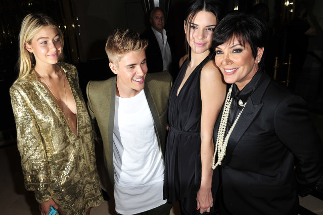 From left: Gigi Hadid, Justin Bieber, Kendall Jenner, and Kris Jenner pose for photographer at the Carine Roitfeld & Stephen Gan celebration of the launch of CR Fashion Book N.5 in Paris, Tuesday, September 30, 2014. (Photo by Zacharie Scheurer/AP Photo)