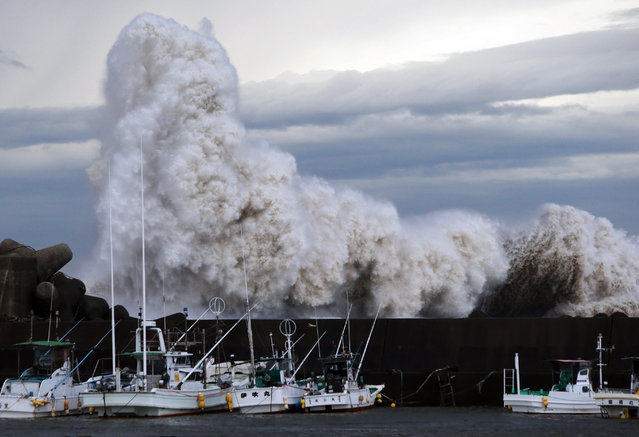 High waves batter a breakwater at a port at Kihou town in Mie prefecture, central Japan on October 6, 2014. Strong typhoon Phanfone slammed into Japan, packing gusts and huge waves that have already swept three US military officials out to sea, as it made a beeline for Tokyo. (Photo by AFP Photo/Jiji Press)