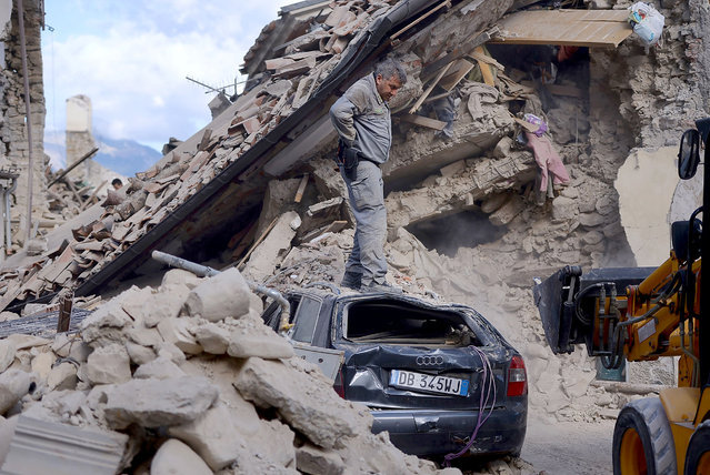 A man stands on top of a damaged car in Amatrice on August 24, 2016 after a powerful earthquake rocked central Italy. (Photo by Filippo Monteforte/AFP Photo)