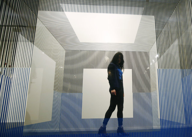 """A visitor poses with artist Jesus R. Soto's artwork """"Cubo de Roma"""" at the Frieze Masters in London, October 14, 2014. (Photo by Luke MacGregor/Reuters)"""