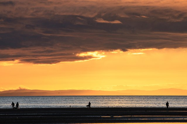 Walkers and shellfish harvesters on North beach in Troon, South Ayrshire, at dusk July 9, 2020. Sunshine and showers are forecast for many UK areas today before a warmer spell next week. (Photo by Cat Perkinton/South West News Service)