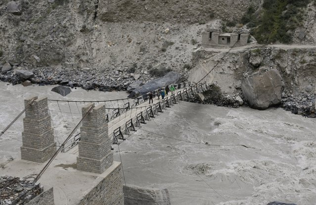 A trekking group walks over a rope bridge across the Braldu River in the Karakoram mountain range near the village of Askole in Pakistan August 27, 2014. (Photo by Wolfgang Rattay/Reuters)