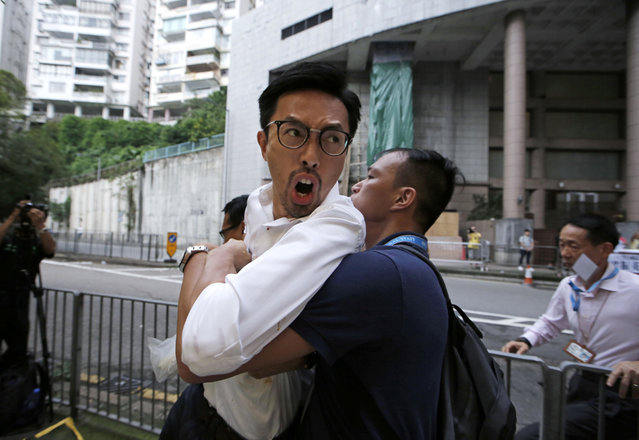 Radical activist candidate Avery Ng, left, is taken away by a police officer outside a polling station for the legislative council election in Hong Kong, Sunday, September 4, 2016. Polls opened in Hong Kong Sunday for the specially administered Chinese city's most crucial election since the handover from Britain in 1997. The vote for lawmakers in the Legislative Council is also the first since 2014 pro-democracy street protests rocked the Asian financial hub. (Photo by Kin Cheung/AP Photo)