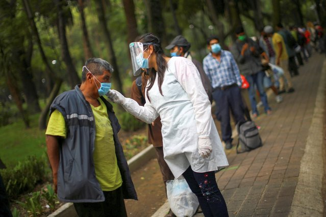 A medical staff scans the temperature of a man lining up for free food at a public park, as the outbreak of the coronavirus disease (COVID-19) continues in Mexico City, Mexico, July 30, 2020. (Photo by Edgard Garrido/Reuters)