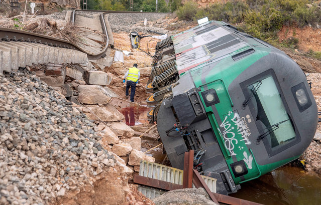 A worker inspect an wagon after it overturned due to the damages caused by heavy rains in a track connecting the towns of Floresta and Vianixa, in Lleida, Catalonia, northeastern Spain, 24 October 2019. Rescue units continue searching five people who are missing since the heavy rainfalls and flood that hit the region in the evening of last 22 October and early morning 23 October. (Photo by Adrian Ropero/EPA/EFE)