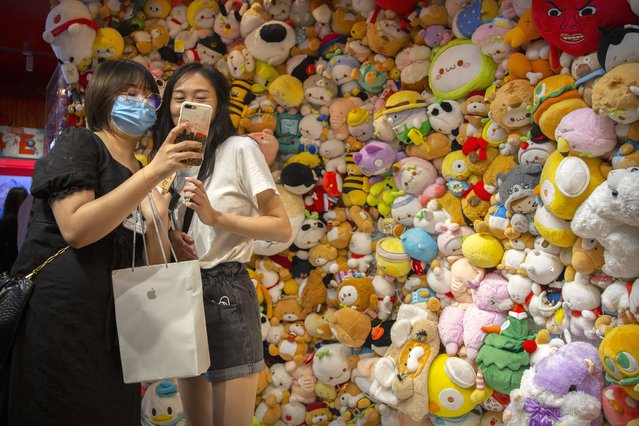 A woman wearing a face mask to protect against the coronavirus poses for a selfie in front of a wall of stuffed animals at an arcade in Beijing, Saturday, August 1, 2020. China reported a more than 50% drop in new cases of COVID-19 on Saturday in a possible sign that its latest major outbreak in the northwestern region of Xinjiang may be waning. (Photo by Mark Schiefelbein/AP Photo)