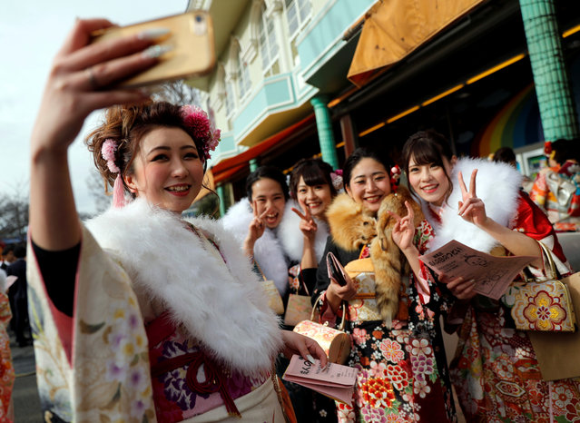 Japanese women wearing kimonos take a selfie as they attend their Coming of Age Day celebration ceremony at an amusement park in Tokyo, Japan January 8, 2018. (Photo by Kim Kyung-Hoon/Reuters)