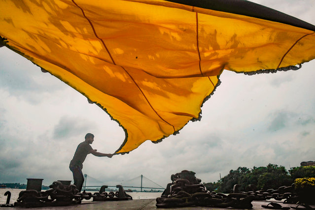 "Muslims dry a traditional triangular flag for the upcoming Islamic festival ""Muharram"" standing on an empty jetty near the Ganges river as the ferry service has been suspended during the first day of the two-day state-imposed lockdown as a preventive measure against the surge in COVID-19 coronavirus cases, in Kolkata on August 20, 2020. (Photo by Dibyangshu Sarkar/AFP Photo)"