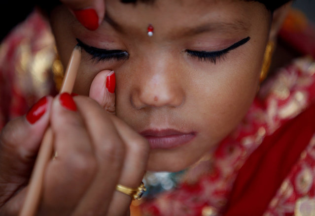 A woman applies makeup to a young girl dressed as the Living Goddess Kumari during the Kumari Puja festival in Kathmandu, Nepal September 14, 2016. (Photo by Navesh Chitrakar/Reuters)