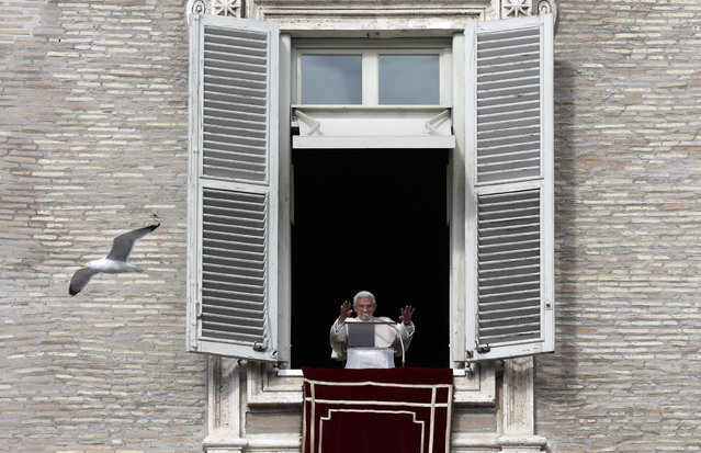 A seagull flies past Pope Benedict XVI delivering his blessing during the Angelus prayer he celebrated from the window of his studio overlooking St. Peter's Square at the Vatican, Sunday, February 3, 2013. (Photo by Alessandra Tarantino/AP Photo)