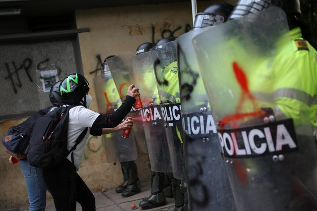 People spray paint on police riot shields as they protest outside a police station after a man, who was detained for violating social distancing rules, died from being repeatedly shocked with a stun gun by officers, according to authorities, in Bogota, Colombia on September 10, 2020. (Photo by Luisa Gonzalez/Reuters)