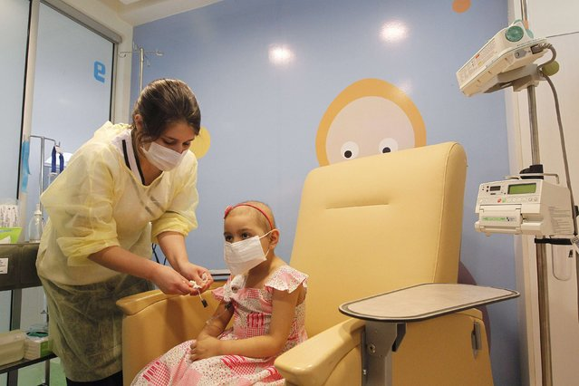 Alexandra Munoz, 5, who lost her hair due to chemotherapy to treat a malignant brain tumor, undergoes a session of treatment with the help of a nurse in the cancer ward of the Luis Calvo Mackenna Hospital in Santiago, October 20, 2014. (Photo by Rodrigo Garrido/Reuters)