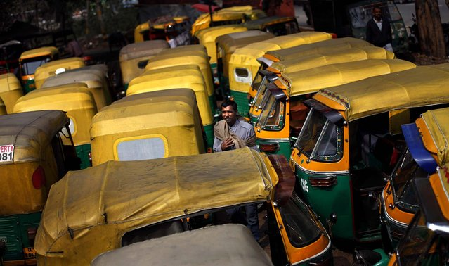 An auto-rickshaw driver stands among dozens of auto-rickshaws parked during a nationwide strike called by trade unions in New Delhi, February 20, 2013. Sporadic violence has broken out in India at the beginning of a two-day strike by labor unions protesting rising prices and government policies to open the economy. Millions of bank and factory workers stayed away from work and public transport was shut down Wednesday after major trade unions called the countrywide strike. (Photo by Altaf Qadri/Associated Press)
