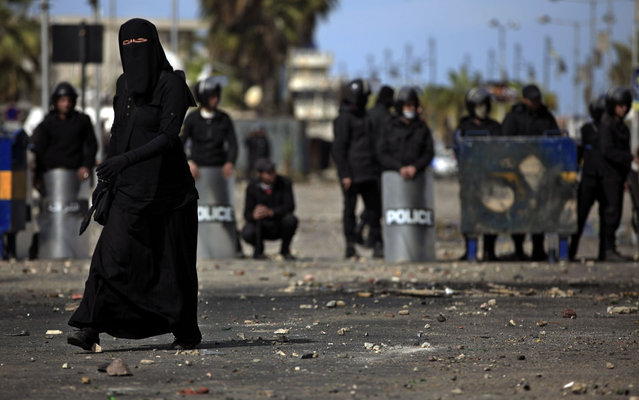 A woman walks past riot police, background, during clashes with protesters, unseen, near a state security building in Port Said, Egypt, Thursday, March 7, 2013. Clashes between protesters and police continued into a fifth day on Thursday in the restive Egyptian city of Port Said. (Photo by Khalil Hamra/AP Photo)