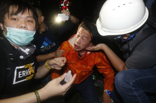 A pro-democracy protester is treated after police used pepper spray during a rally close to the chief executive office in Hong Kong, November 30, 2014. (Photo by Bobby Yip/Reuters)