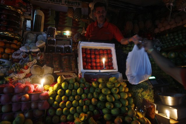 A fruit seller works in candlelight to mark Earth Hour in a shopping district of Bangalore, India, Saturday, March 23, 2013. Earth Hour was marked worldwide at 8.30 p.m. local time and is a global call to turn off lights for 60 minutes in a bid to highlight the global climate change. (Photo by Aijaz Rahi/AP Photo)
