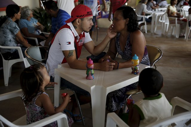 Prisoner Cleverson Barbosa, 27, (L) caresses his wife's face as their children sit watching, during a half-day visit as part of the ACUDA programme, at a complex of ten prisons in Porto Velho, Rondonia State, Brazil, August 28, 2015. (Photo by Nacho Doce/Reuters)
