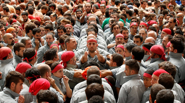 """Castellers de Sants start to form a human tower called """"castell"""" during a biannual competition in Tarragona city, Spain, October 2, 2016. (Photo by Albert Gea/Reuters)"""